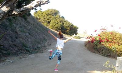 A student skipping along a hiking trail