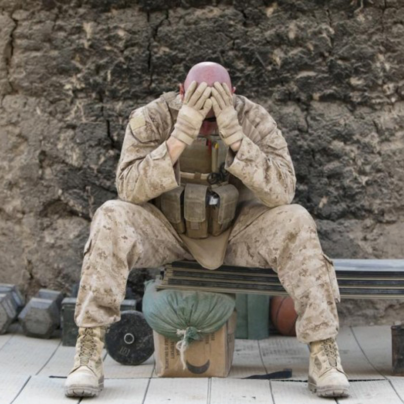 A soldier sitting with his head in his hands
