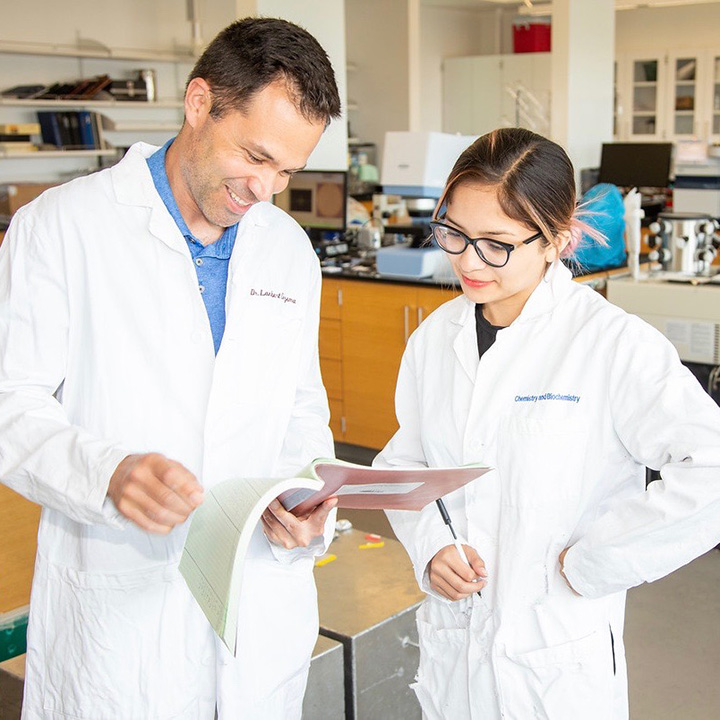 A professor and student looking at a chart in a laboratory while wearing lab coats and protective goggles